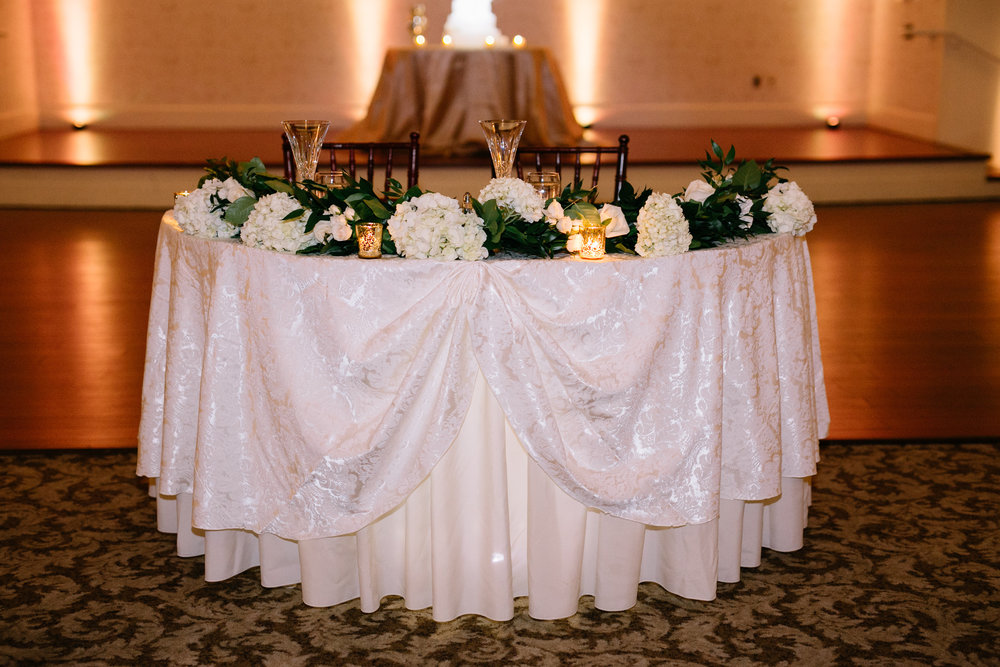 Sweetheart table at wedding reception with crystal flutes