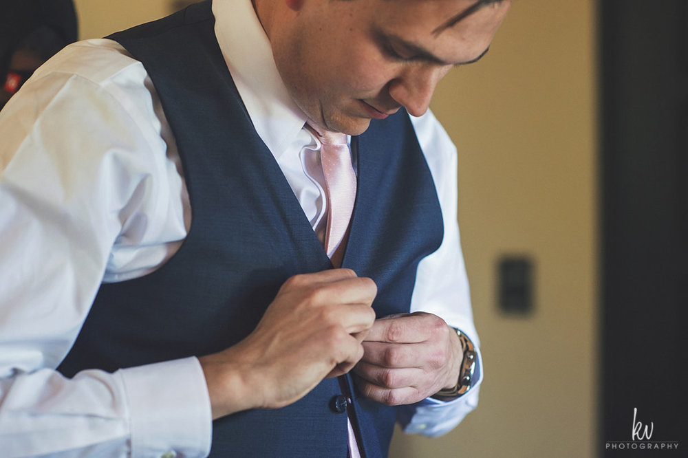 Paul buttoning up his vest before he meets his bride