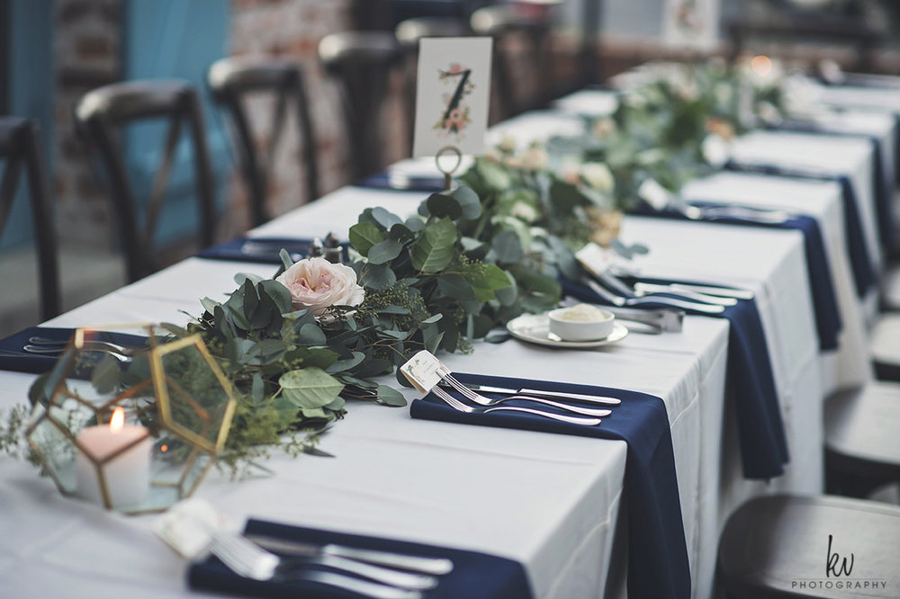 Navy linen napkins, blush roses, gold terrariums