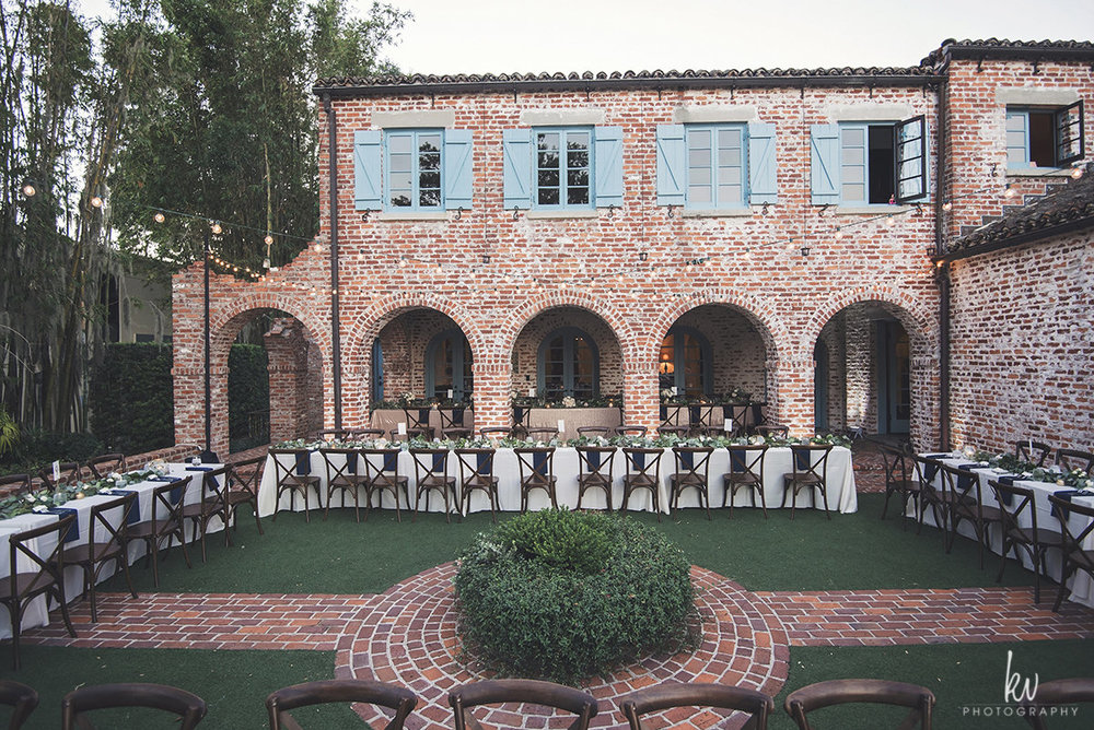 Banquet tables with wooden chairs, outside lawn wedding reception