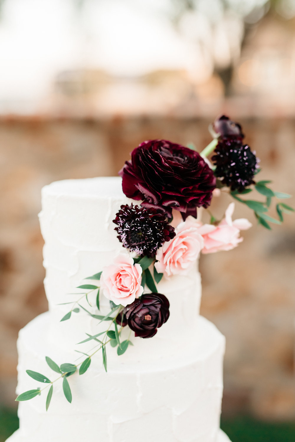 Romantic wedding cake with blush and deep red florals