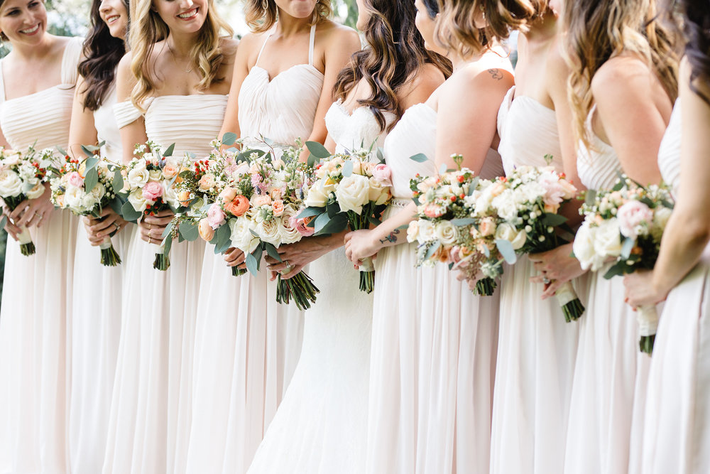 Bridesmaid bouquets with blush spray roses and peach ranunculus