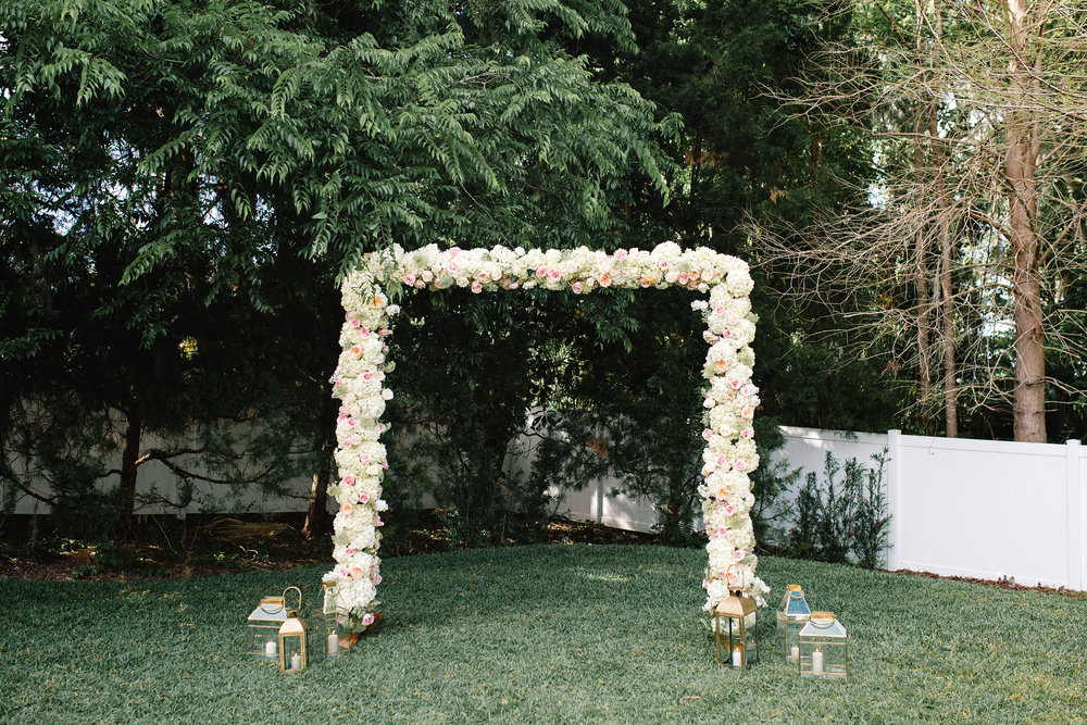 Ceremony arbor with ivory hydrangea and blush garden roses