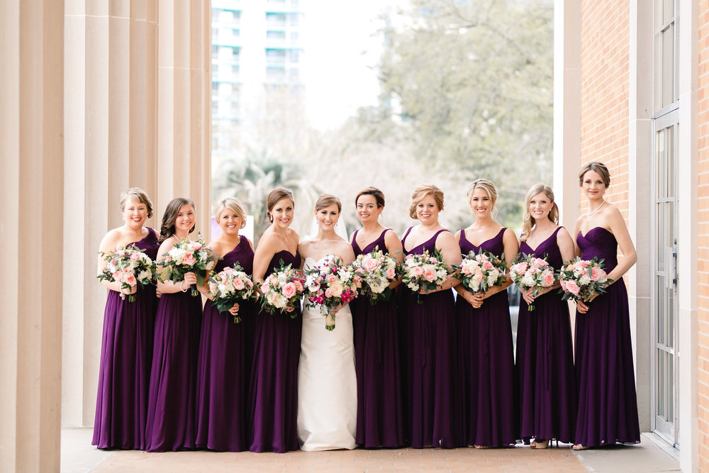 Bride with her bridesmaids in deep plum dresses