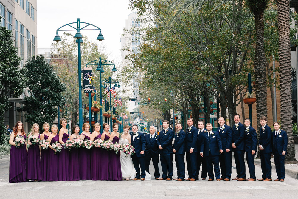Bridesmaids in deep purple dresses and groomsmen in navy suits, Downtown Orlando