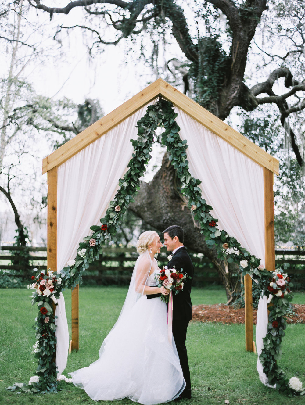 Wedding ceremony arch with garland, red and blush garden roses