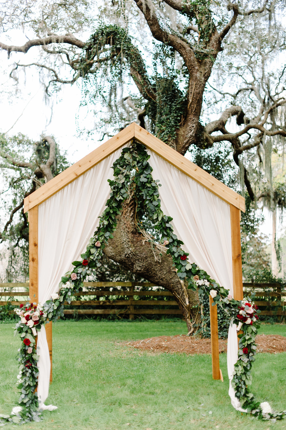 Custom wooden ceremony arch, complete with garland and drapery by Blue Ribbon Weddings
