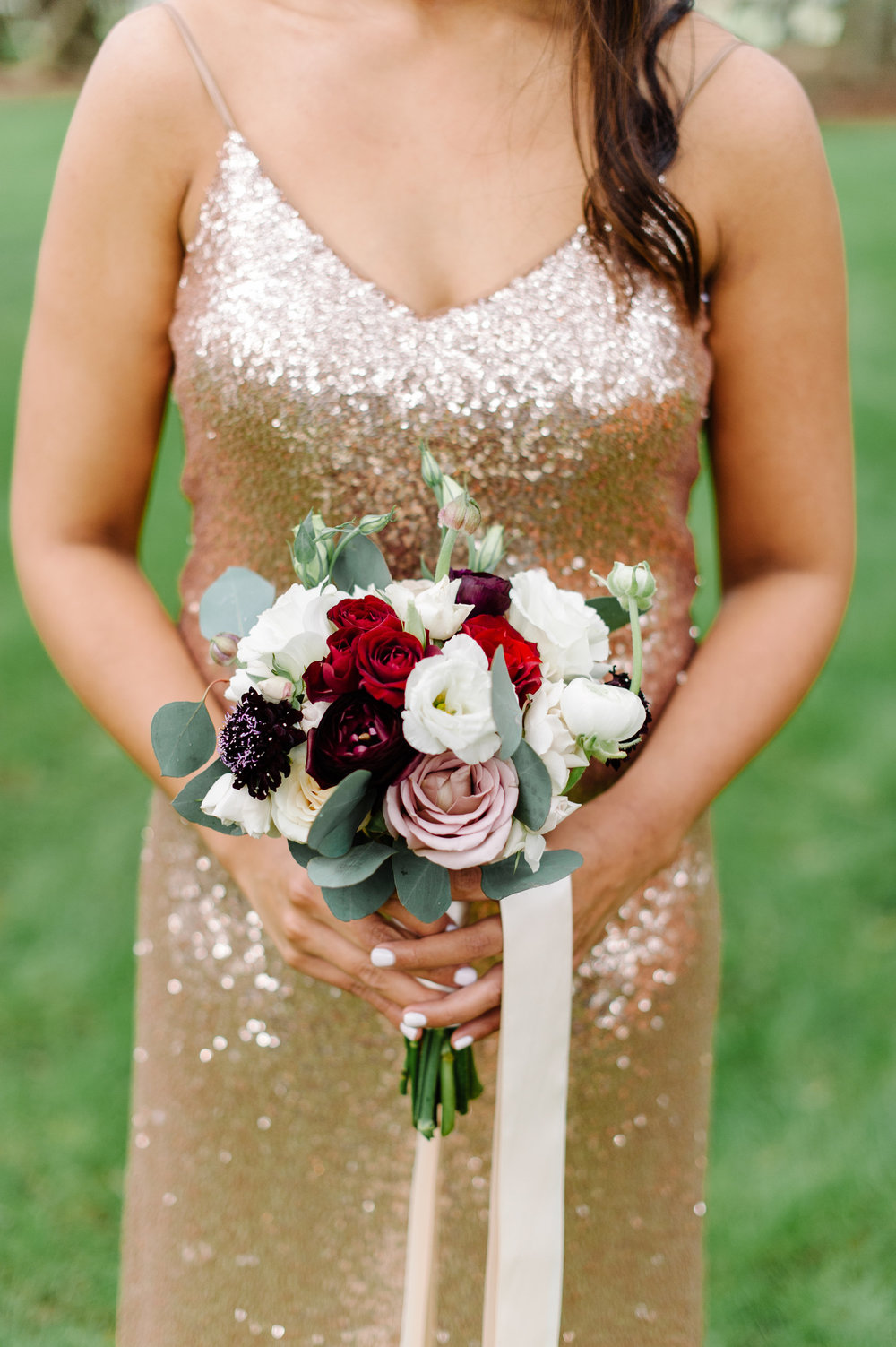 Gold glittered bridemaid dress with bouquets, comprised of red spray roses and ivory rannulus