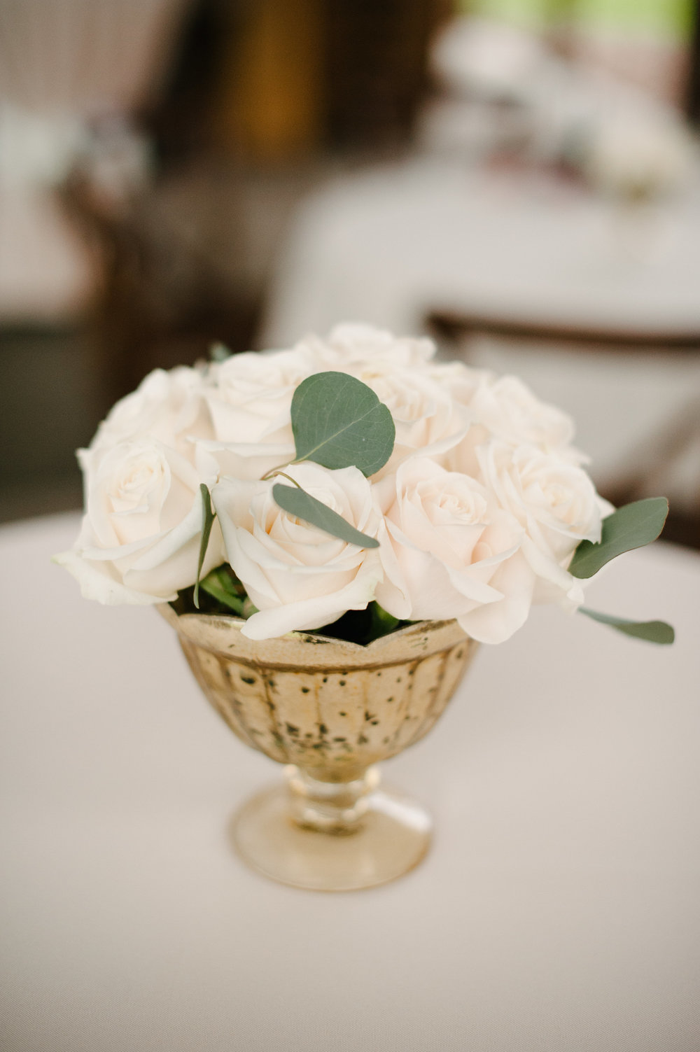 Reception centerpieces of ivory garden roses in mercury gold vases