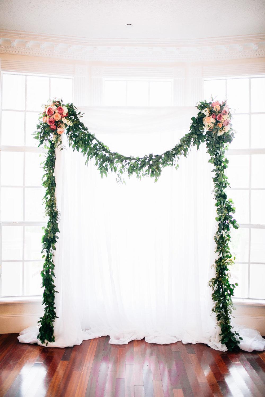 Eucalyptus floral arch indoor ceremony at Luxmore Grande, Orlando Wedding Planner