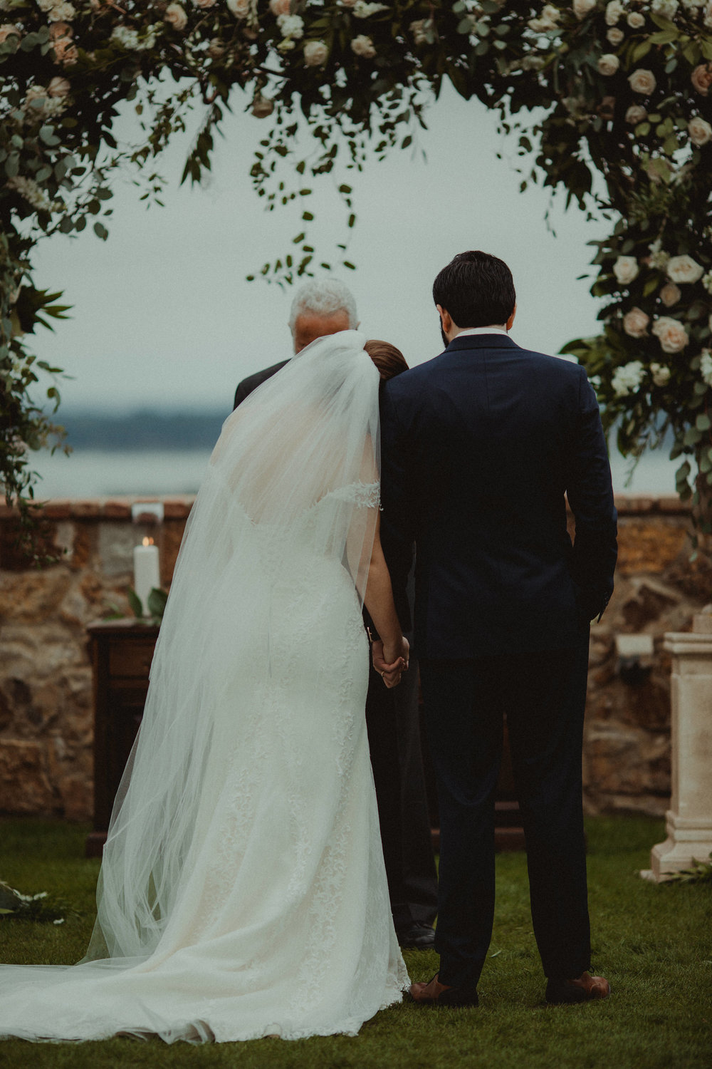 Outdoor wedding ceremony encircled by roses with a lakeside view