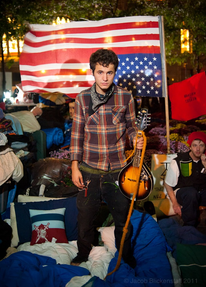 #occupywallstreet KV, a musician sleeping in Zuccotti Park, stands in front of a defective American flag manufactured in China and bought at Walmart. 10/5/11