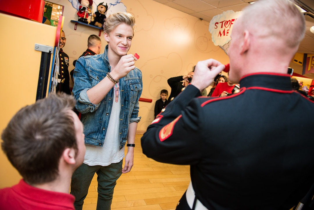 "Cody Simpson makes a bear with a Marine for Build A Bear Workshop's ""Stuffed With Hugs"" program benefiting  Toys for Tots ."