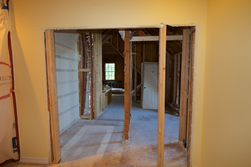 In this pic, I was standing at the end of the upstairs hall. On the very left, you can see some of the plastic that they put up over stairway entry. We're looking at the new entrance into the studio wing. The entry will be french doors. The framing that you see just inside the attic, almost in the middle, is what remains of the linen closet. Our alarm system is at the top of that wall. Until Advanced Alarms makes it out here on Thursday and moves the panel, that framing has to stay. That grayish, striped wall on the left of that framing, is the stairwell, minus the insulation.