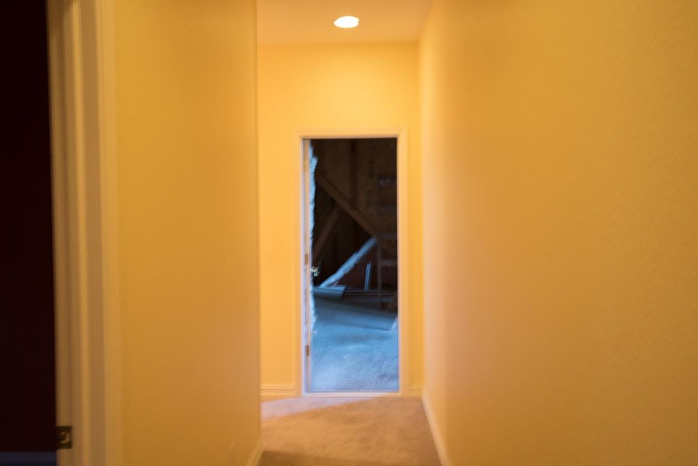 Before construction: Attic door at end of hallway.