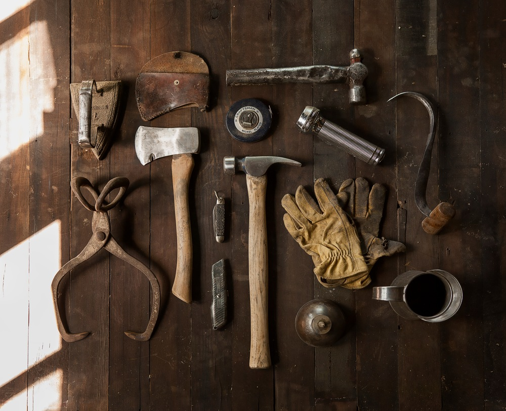 Process payroll for Construction industry by showing dirty gloves and hammer and other tools.