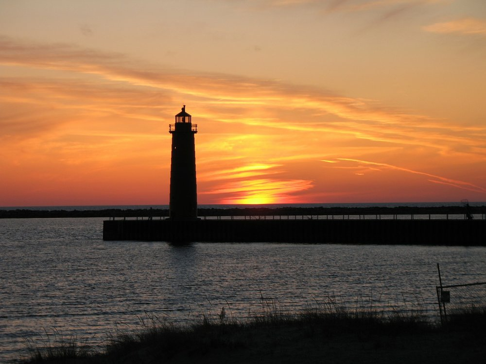 Dominion Systems has office in West Michigan represented by lighthouse near water with orange sunset in the sky.