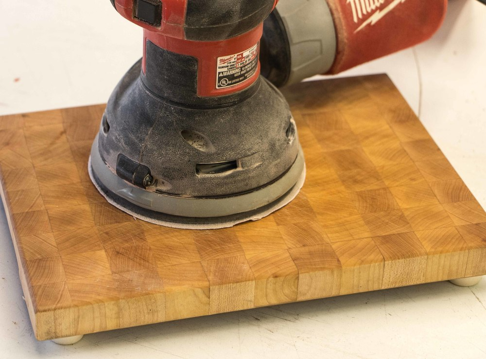 using an orbital sander with rough grit sandpaper to begin removing scratch marks