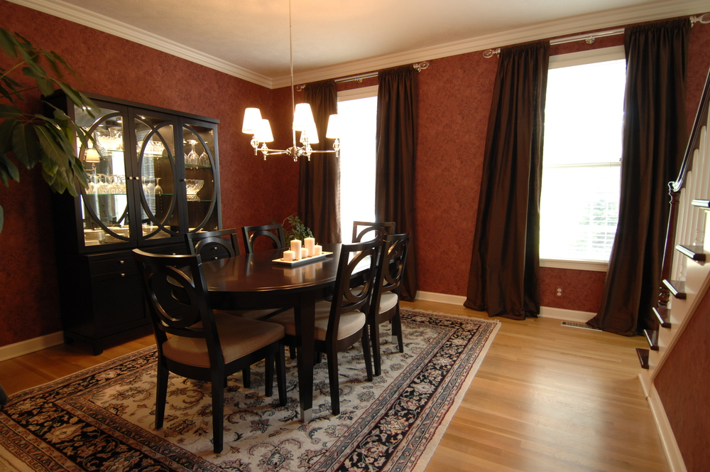 In the dining room, we worked with the existing wall covering and rug, and added new furnishings, lighting and window treatments.
