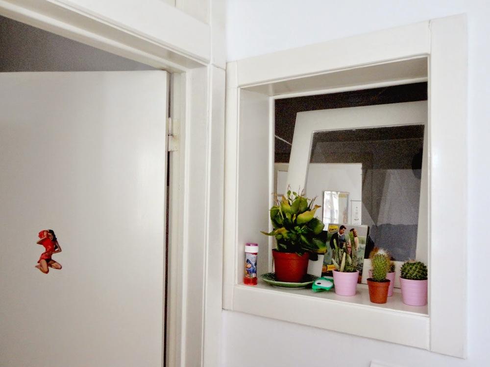 É a pin-up que nos indica a casa de banho - palavras para quê? Esta pequena janela dá para o quarto, que deve ser o quarto interior com mais luz que conheço até hoje (tem duas portas, uma das quais em vidro e esta janela).