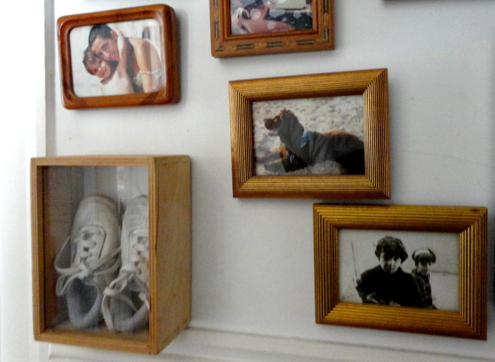 entre as fotos e pinturas ainda há espaço para os primeiros sapatos do filhote Thomas.