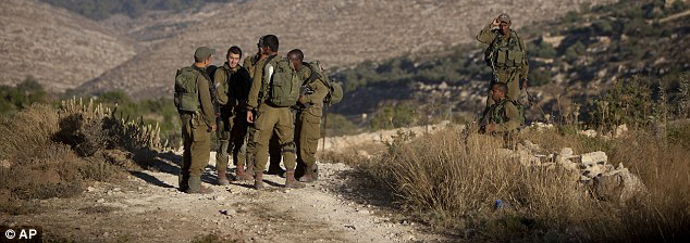 Location: Israeli soldiers stand near the area where the three Israeli teenagers' bodies were found yesterday.   The rural track is just outside the village of Halhul, a few miles north of the West Bank city of Hebron               Photo Credit: DailyMail