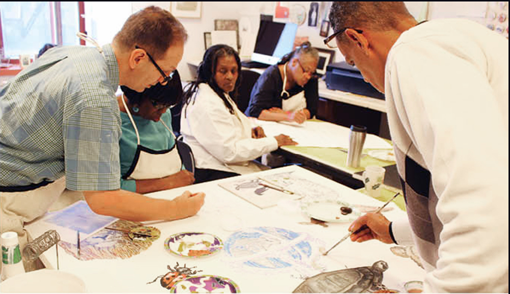 Jerald Frampton assists a group of ElderCare clients at Odyssey House's 121st Street art studio.