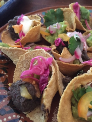 Tacos cups with green chile black beans, pickled cabbage and queso fresco