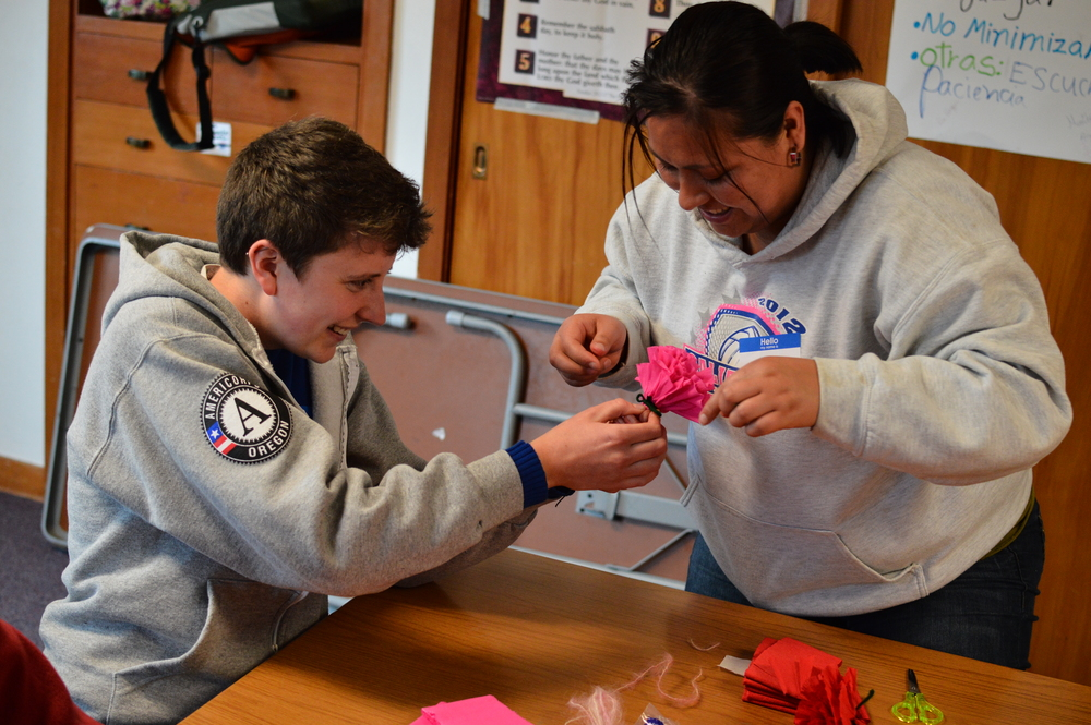 Angela learning how to make paper flowers for an Adelante Mujeres float