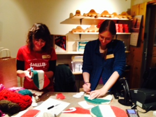 Kate and Kara cutting HBC blanket scraps in Christmas shapes.