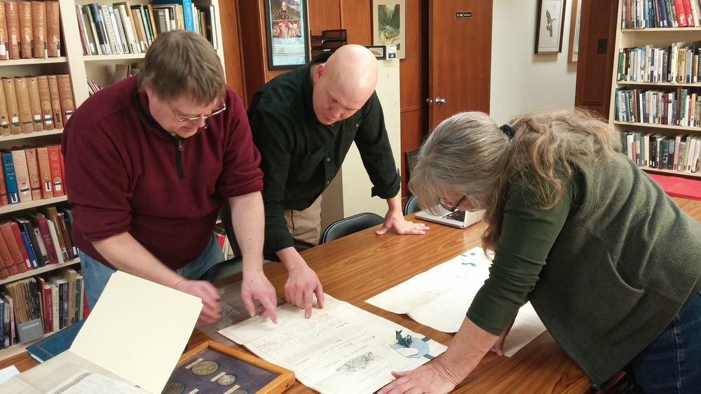 Don Willcock of Trent Valley Archives (left), Basia Baklinski of The Conservation Clinic (right) and Canoe Museum Curator Jeremy Ward (centre) assessing the MacGreggor collection