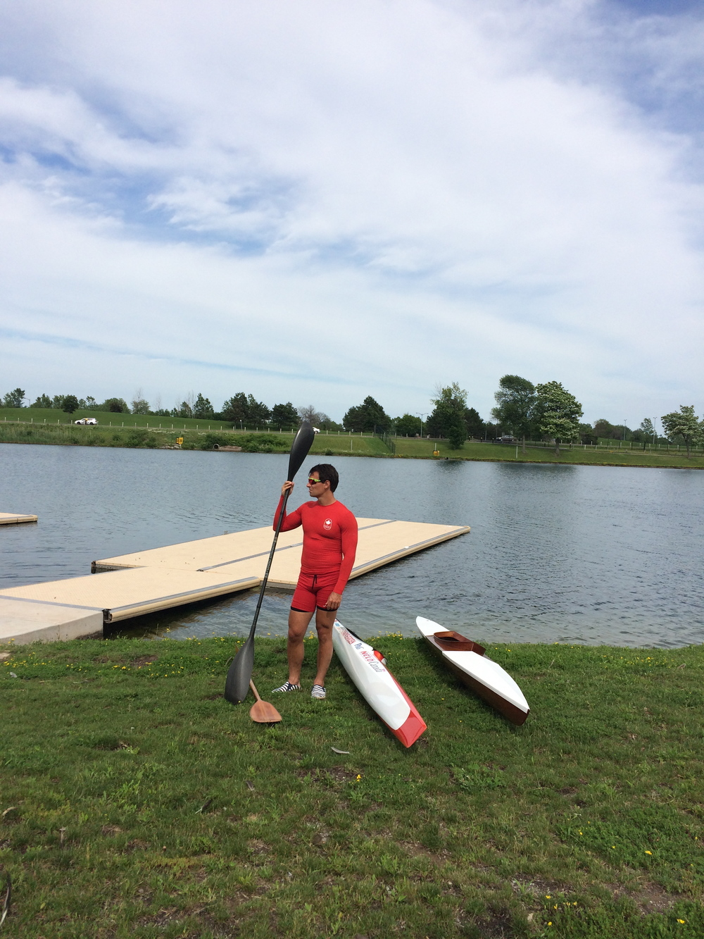 Adam van Koeverden with his modern sprint kayak and the 1940's kayak restored by Jeremy Ward