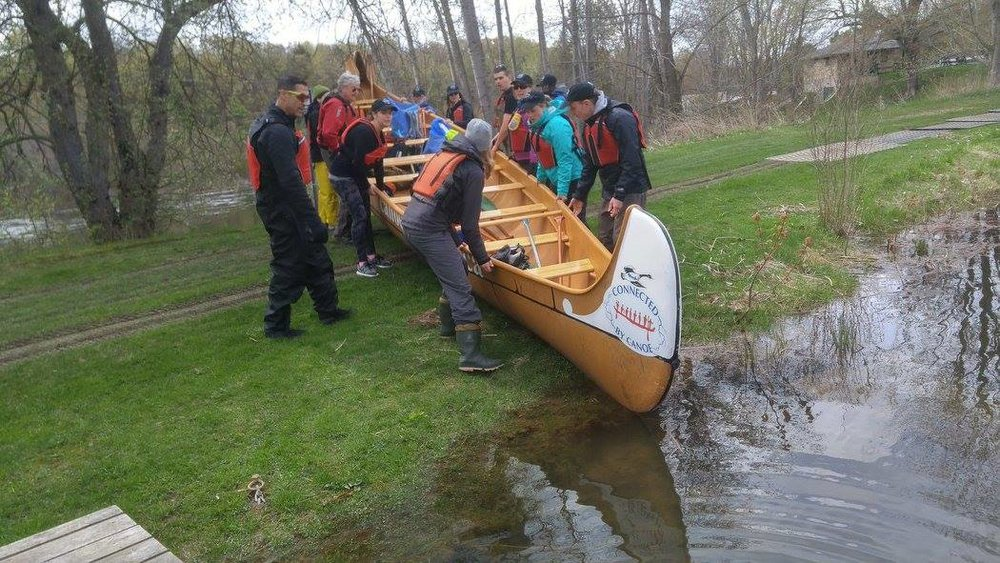 participants launching the canoe into the water