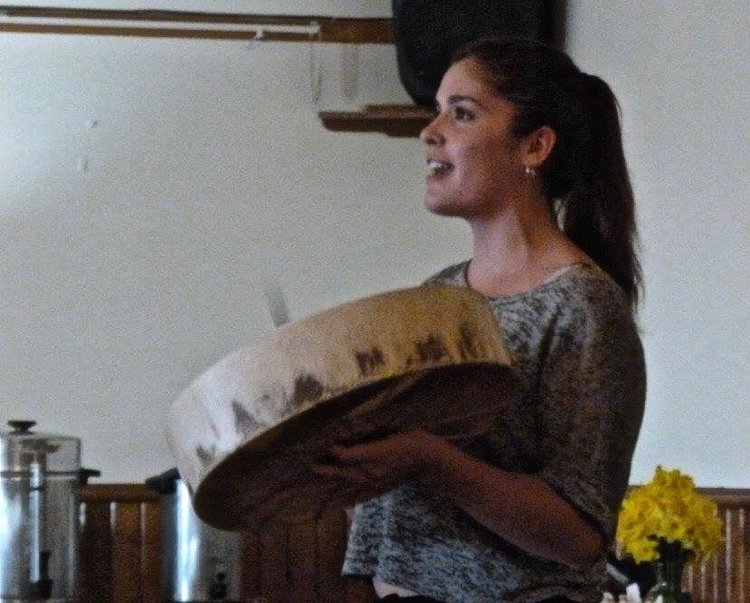 a woman singing and playing a ceremonial drum