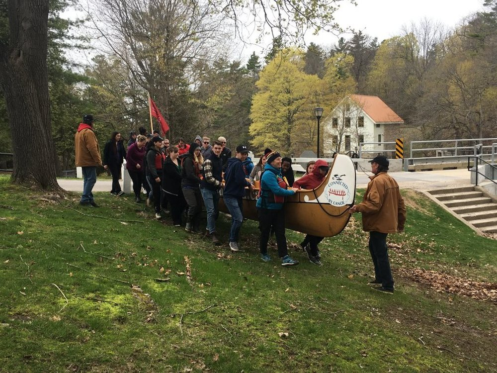large group of people help to carry the canoe to the water