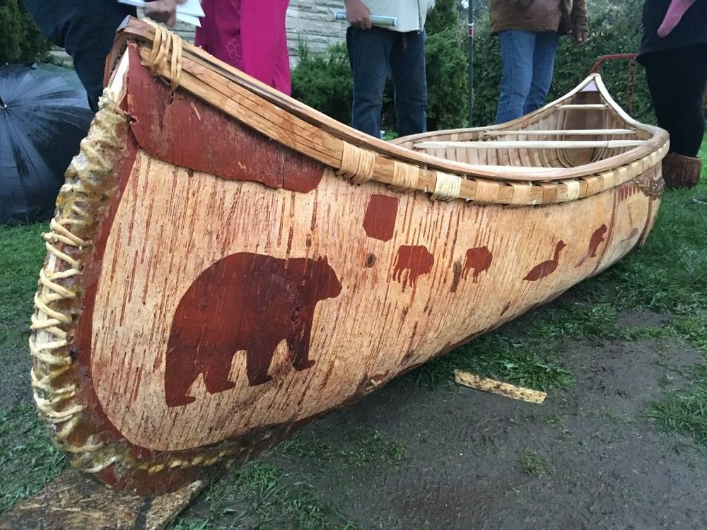 birchbark canoe decorated with bears and other wild animal pictures