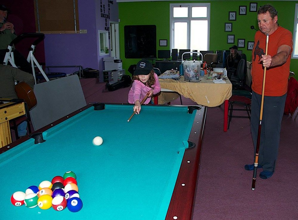 an older man and a young girl playing pool together