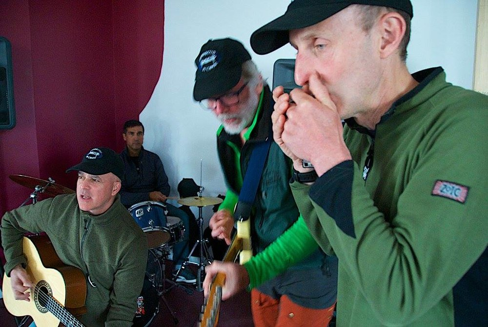 three men playing musical instruments, one is playing guitar, on is playing an electric guitar and one is playing a harmonica
