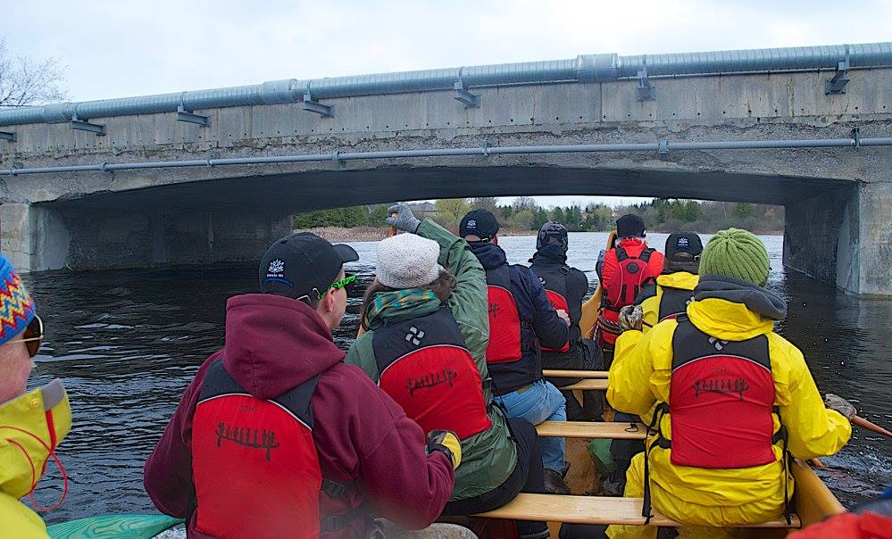 paddlers going under a bridge in the canoe