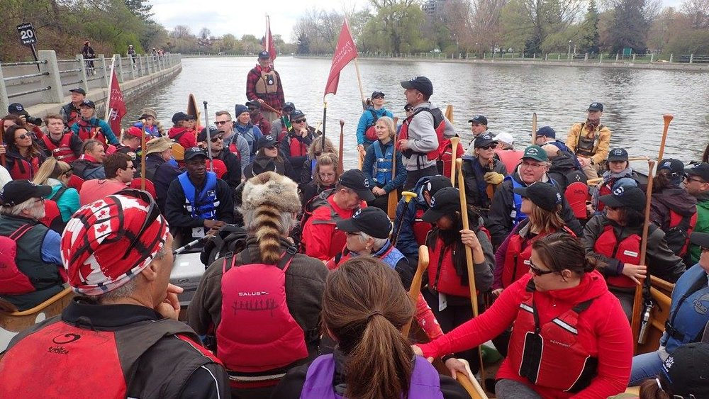 canoes rafted together at the waterway's edge to talk