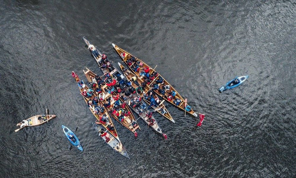 overhead shot of 5 large canoes with participants and a couple smaller canoes and kayaks all raft together on the water