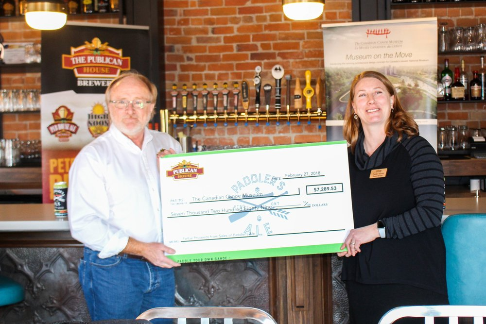 Marty Laskaris (left) presents Carolyn Hyslop with partial proceeds from sales of Paddler's Ale.