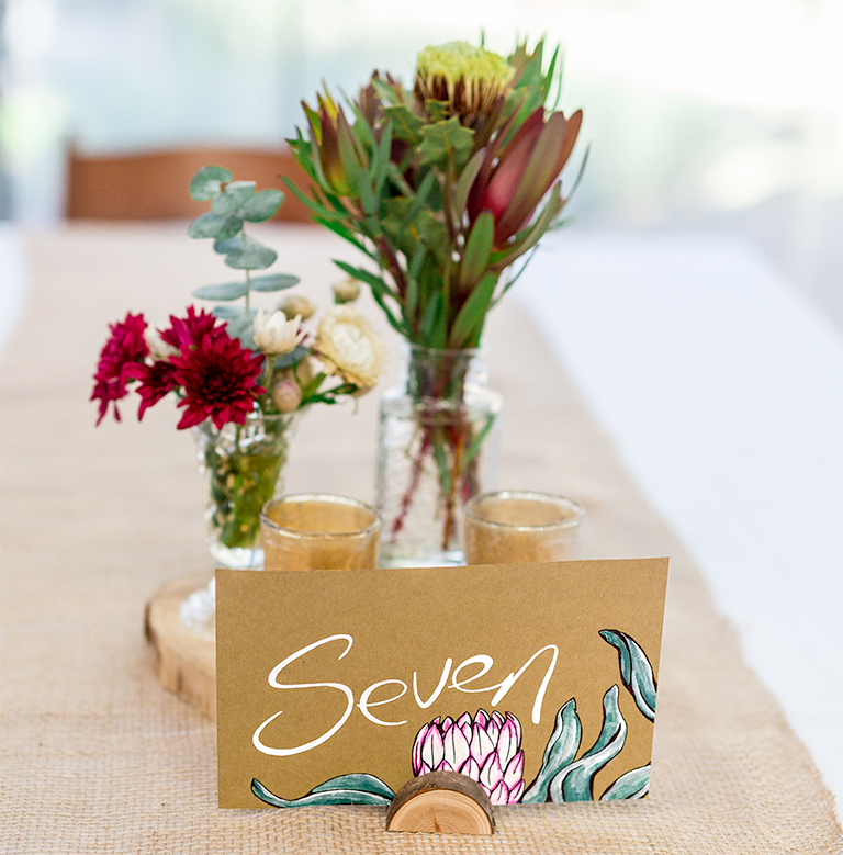 Hand painted table sign featuring a King Protea