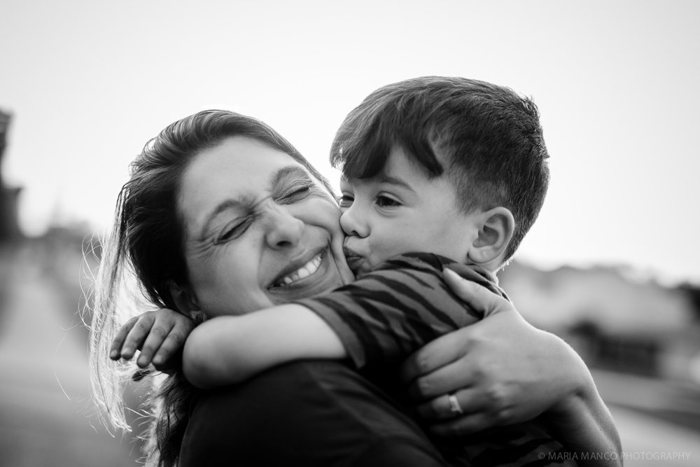©MariaManco _ Boy gives smiling mom a hug and kiss