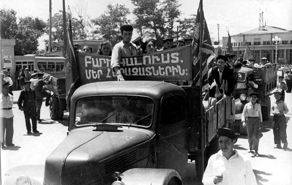 """Армения встречает репатриантов. Надпись на транспаранте""""Доброго света нашим родным""""."""