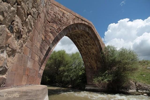 Древний армянский одноарочный мост через пенящийся распластанный по камням голубой поток. Фотоwiki-turizm.ru