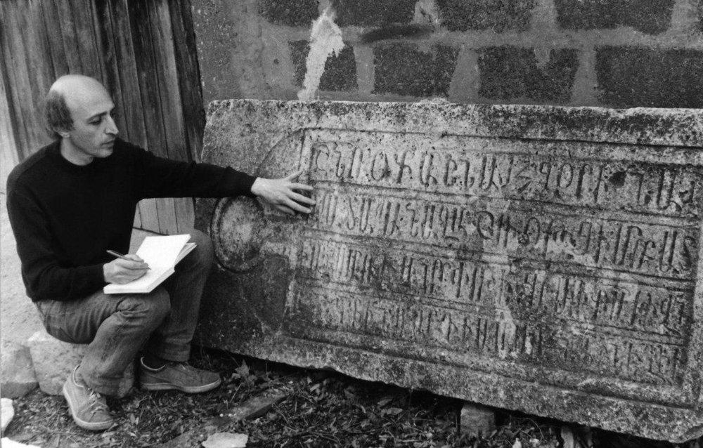Исследователь-сербист, писатель и поэт Бабкен Симонян расшифровывает надписи на армянском надгробии с кладбища в Белграде. Фото Спутник-Армения