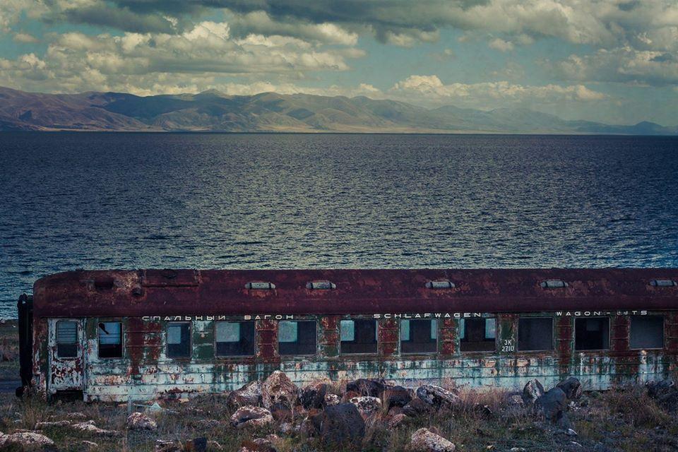 На берегу Севана, как будто упавший с луны, стоит ржавый спальный вагон. фото Петра Ловыгина