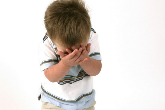Crying boy with hands over face.