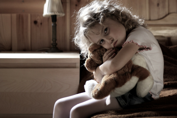 Sad looking child hugging teddy bear.